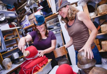 Nora Swan and Sam Stone (in brown tank) of Swan and Stone Millinery create colorful hats in Brandon, Vermont.