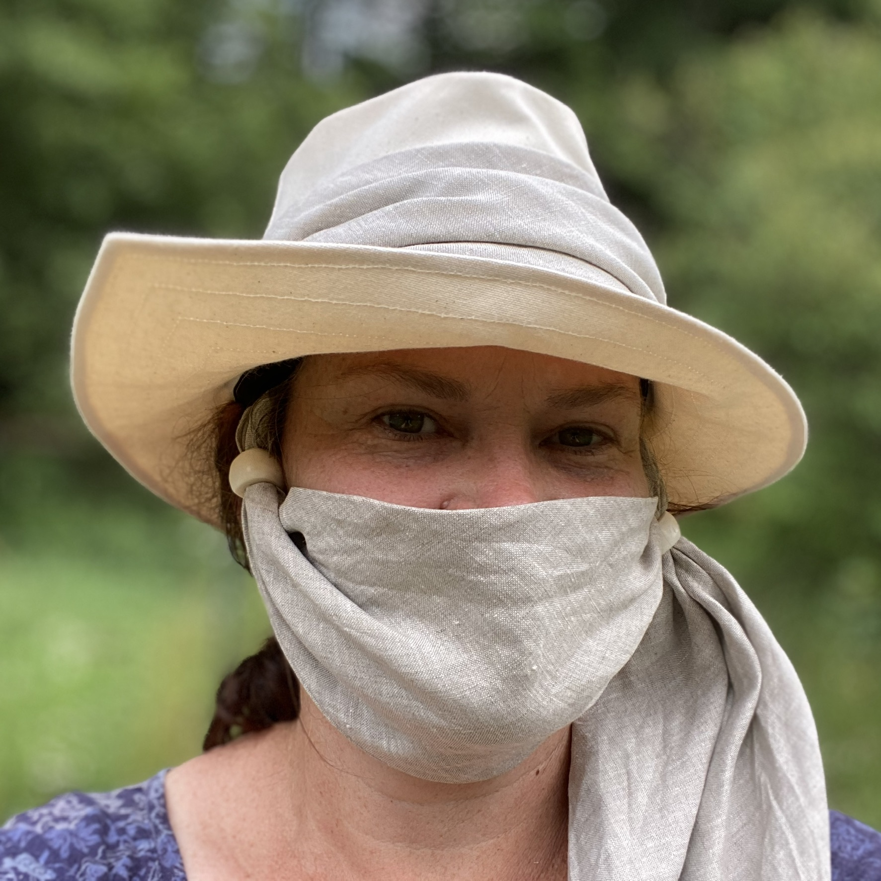 A lady wearing a fabric hat and a scarf on her face.