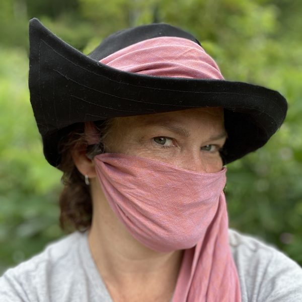 A lady wearing a black fabric hat and pink scarf on her face.