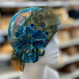 Picture of a colorful ladies hat with a peacock feather on it.